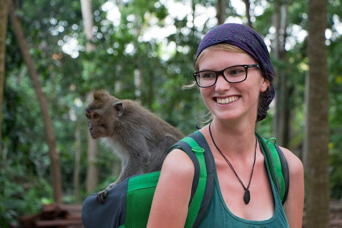 Ein Affe auf Binas Rucksack im Affenwald von Ubud auf Bali in Indonesien