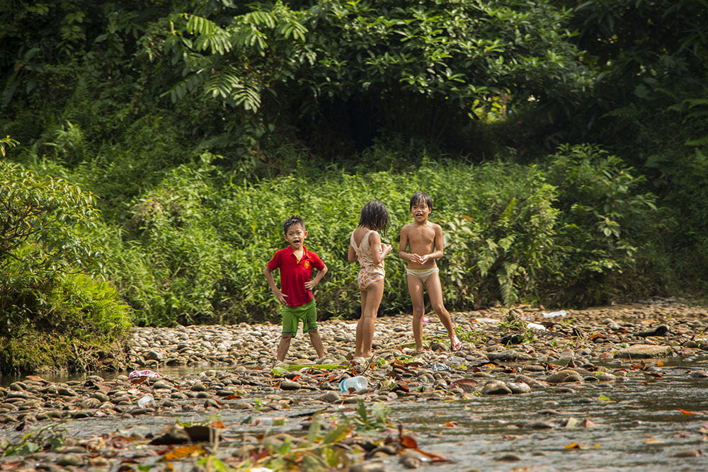 Malaiische Dorfkinder spielen am Fluss