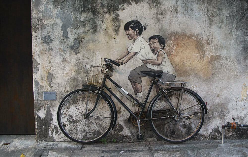"""Kids on Bicycle"" - Berühmtes Motiv mit zwei Kindern auf einem Fahrrad in Georgetown (Penang)"