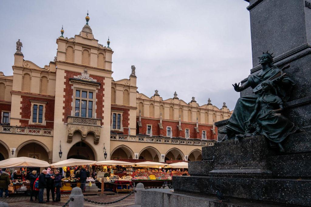 Das Adam-Mickiewicz-Monument in Krakau mit den Tuchhallen im Hintergrund